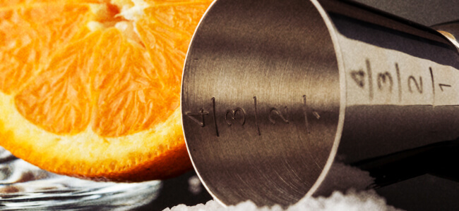 Close up view of a jigger next to a sliced orange.