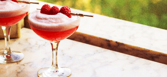 Red cocktail served in a coupe glass and garnished with raspberries.