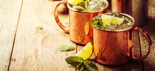 A pair of Moscow mule cocktails served inside of copper mugs.