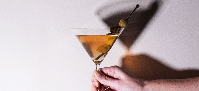Hand holding a martini glass that is casting a shadow on the wall behind it.
